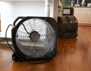 Water damage in kitchen with industrial fans and dehumidifier running to dry out leak damage.
